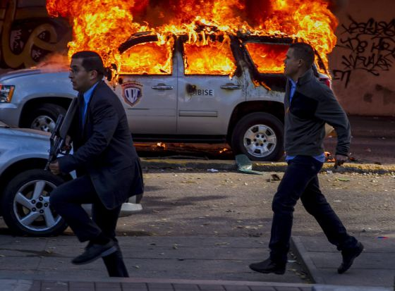 Forensic police officers walk past a vehicle ablaze in Caracas on Wednesday.