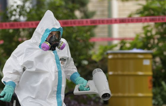 A hazmat worker cleans outside the apartment building of the infected hospital employee on Sunday.