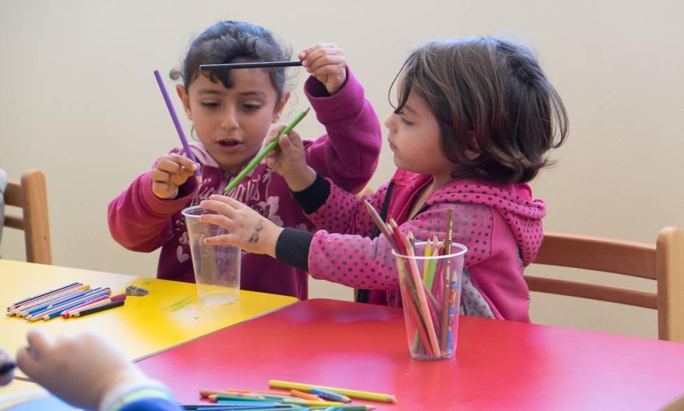 Dos niñas juegan con lápices de colores en una de las aulas.