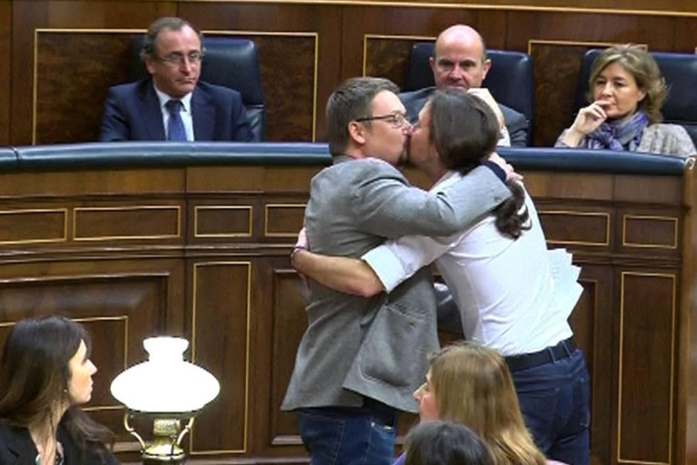 El líder de Podemos, Pablo Iglesias, y el de En Comú Podem, Xavier Domènech, se besan en el Congreso durante la segunda jornada del debate de investidura del líder socialista.