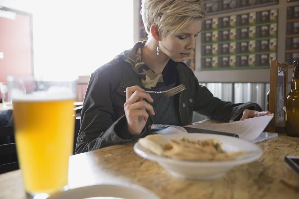 Una mujer come mientras lee.