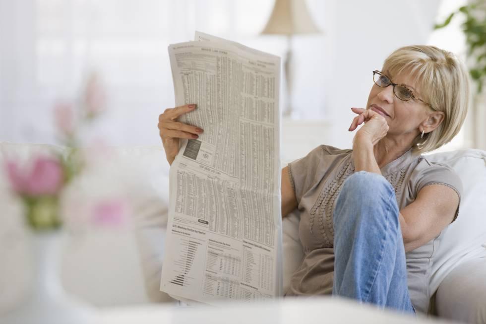 Una mujer leyendo el periódico.