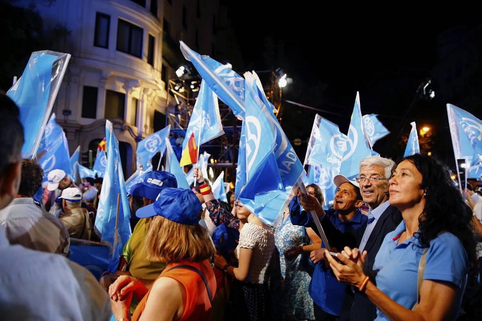 Simpatizantes del Partido Popular junto a su sede en la madrileña calle Génova tras conocer los primero resultados electorales.