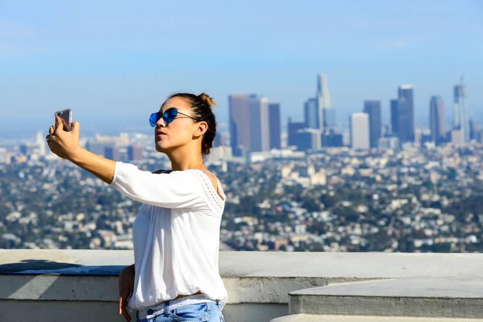 """Una mujer joven se toma un """"selfie"""" desde el observatorio Griffith con la ciudad de Los Ángeles detrás, en California (Estados Unidos)"""