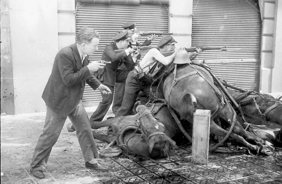 Un grupo de guardias de asalto apostados tras unos caballos muertos como barricada