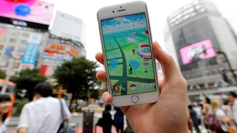 Usuário joga o Pokémon Go com o celular em uma movimentada rua de Tóquio.