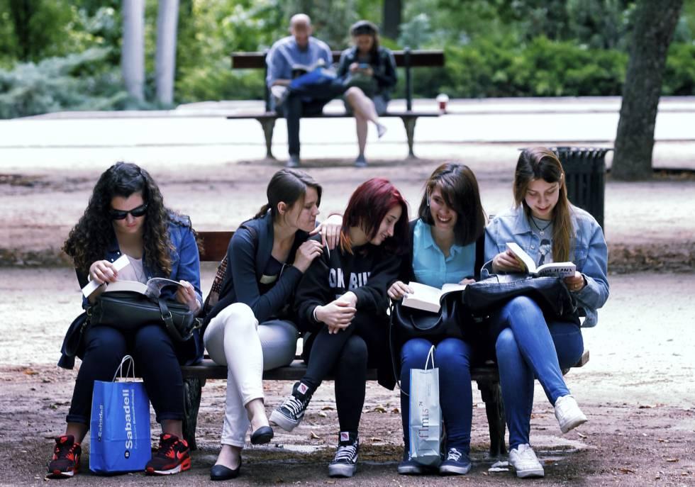 Un grupo de jóvenes lee en un banco en la Feria del Libro de Madrid.