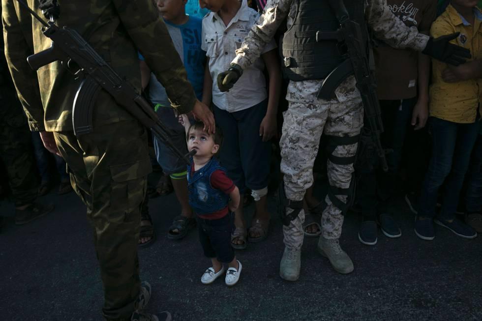 Un niño mira a un miembro de las Brigadas de Al Qassam, rama militar de Hamás, durante un desfile antiisraelí.