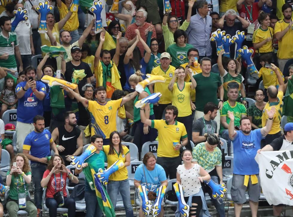 Fanáticos de Brasil apoyan a su equipo durante la final de voleibol masculino entre Brasil e Italia en los Juegos de Río 2016