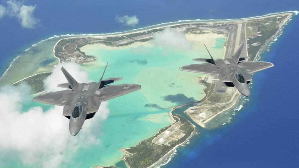 Dois caças F-22 Raptor sobrevoam as três ilhas em U do atol de Wake.