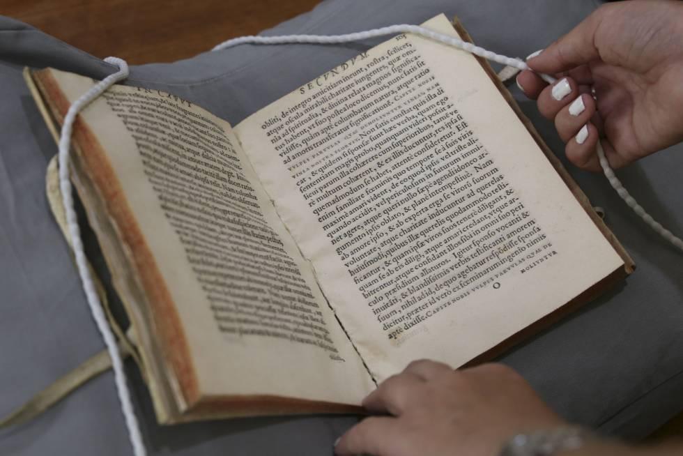 Un libro de la Biblioteca Nacional y el separador de hilo utilizado para marcar las páginas que se desean reproducir.