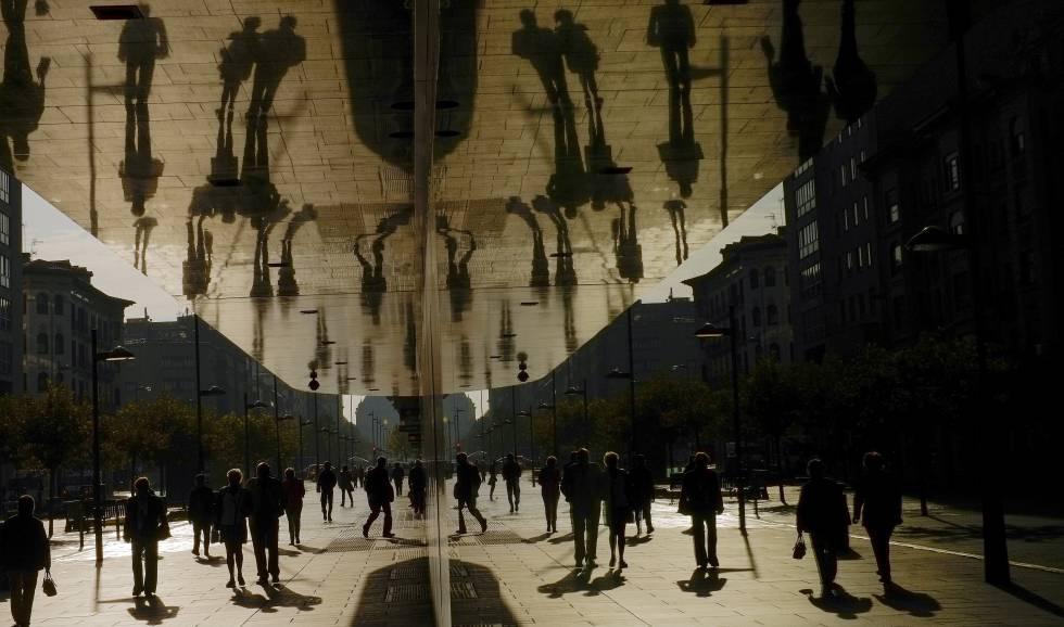 Siluetas de personas se reflejan en los espejos de un edificio.