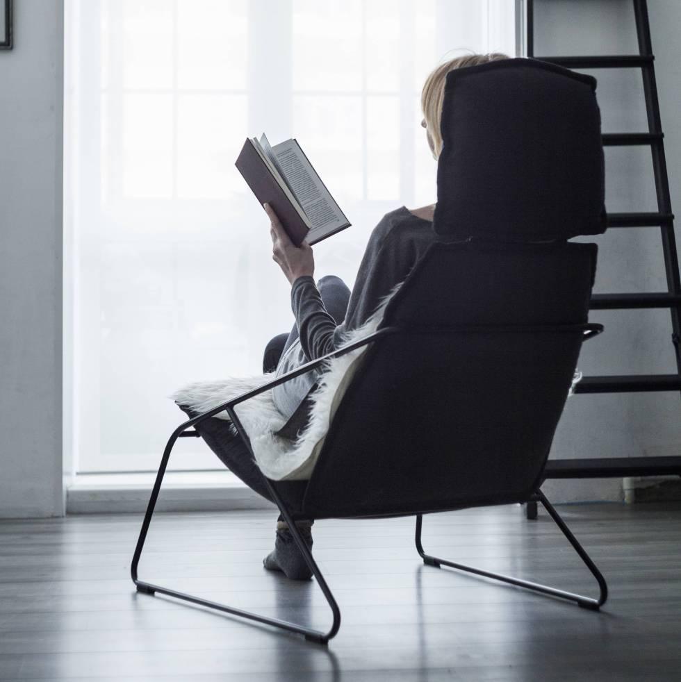 Persona leyendo sentada en un sillón.rn rn