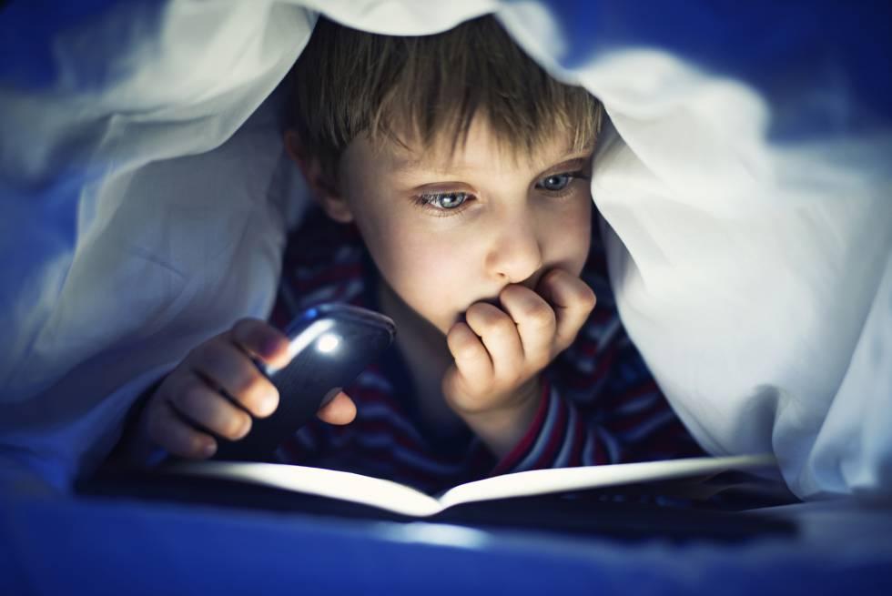 Un niño leyendo un libro iluminado por la luz del móvil