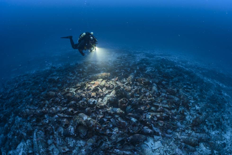 A diver examines the remains, which are covered by hundreds of amphorae.