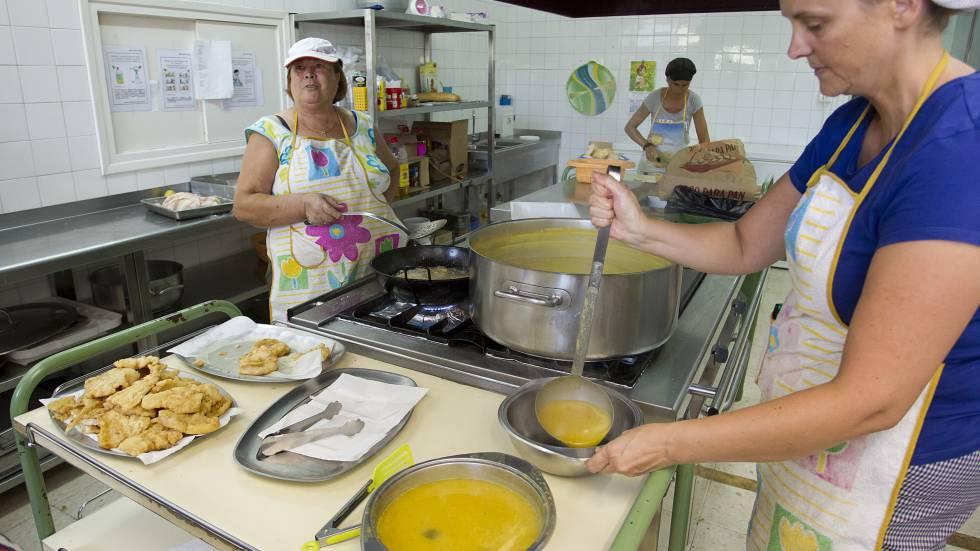 Dos voluntarias preparan sopa de verduras en un campamento de verano para niños sin recursos.