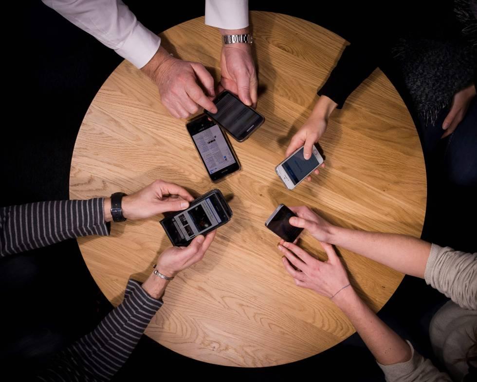 Varias personas utilizando sus teléfonos móviles