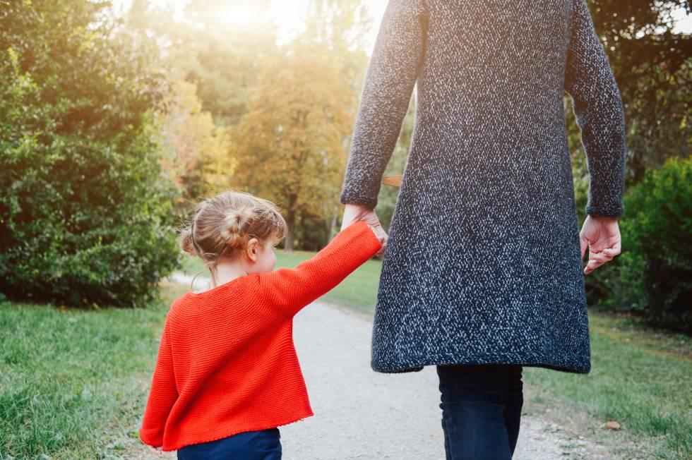 Una madre caminando con su hija por el parque