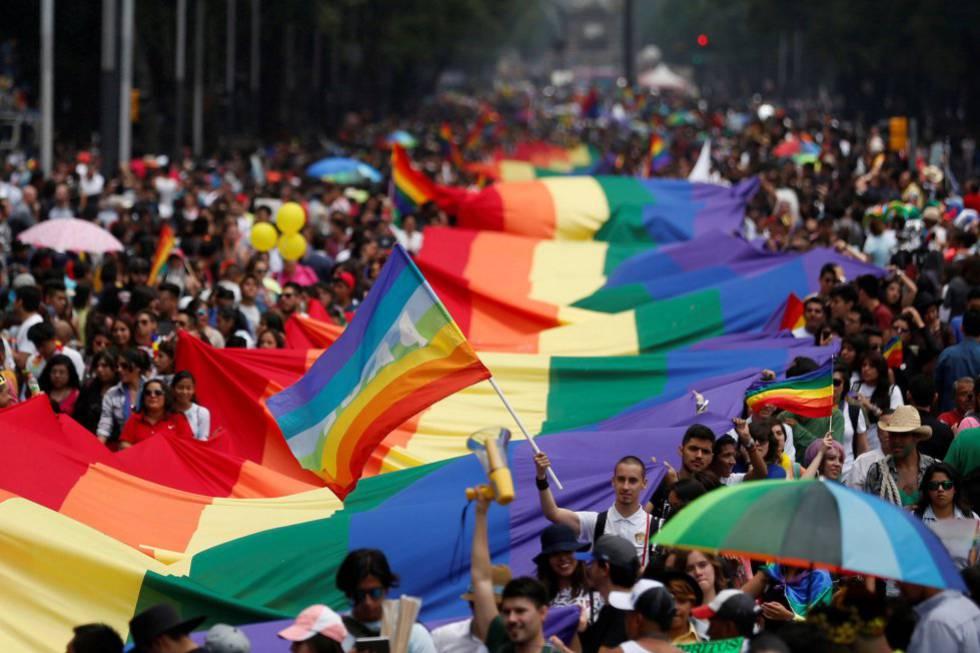 Os participantes do desfile anual do dia do orgulho gay sustentam uma grande bandeira de arco íris na cidade de México.