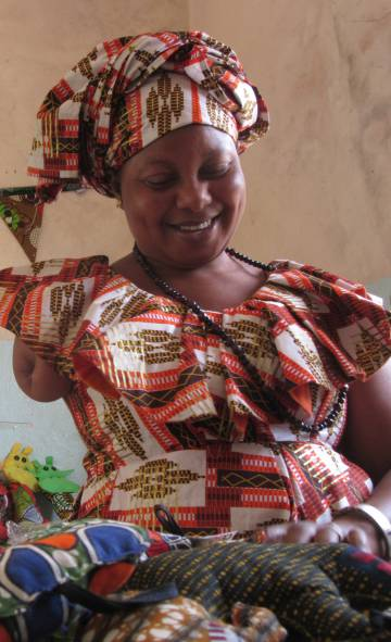 Aisatou Doumbia, presidenta del Grupo de Interés Económico Deggo de Kolda, junto a los productos que elaboran.