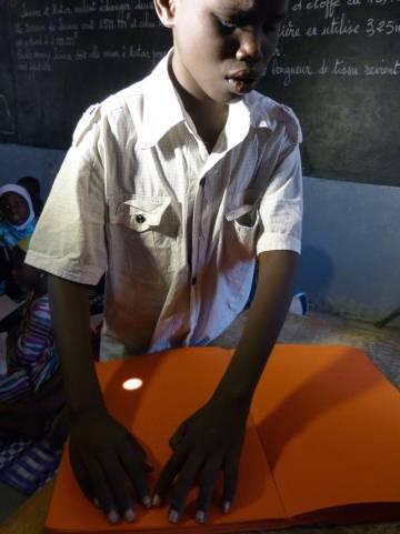Un menor invidente lee braille en un centro cofinanciado por la UE en Dakar.