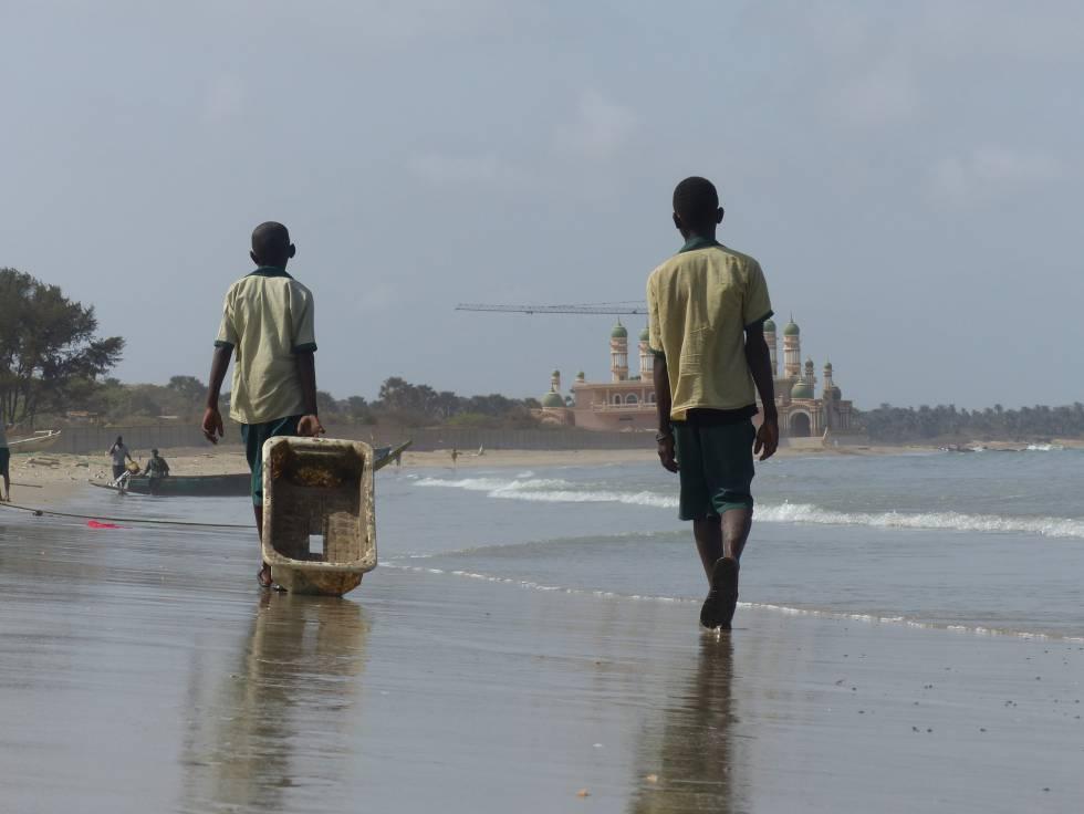 Dos niños van a recoger residuos en la playa de Gunjur, Gambia.