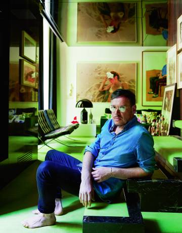 Jordi Labanda en las escaleras que suben a su dormitorio. Obras de David Hockney y Ryan McGinley decoran la pared del fondo.