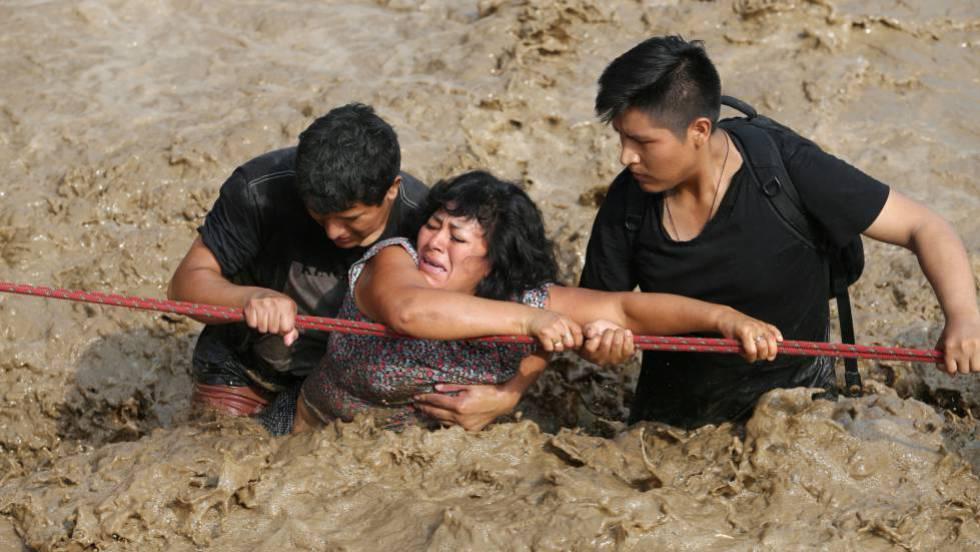 Una mujer es ayudada a salir de una riada en Huachipa, Perú, el pasado marzo.