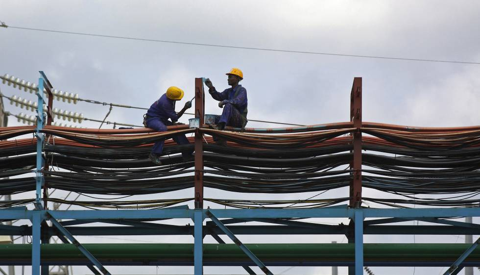 Dos operarios trabajan en el mantenimiento de una central de energía térmica en Takoradi, Ghana.