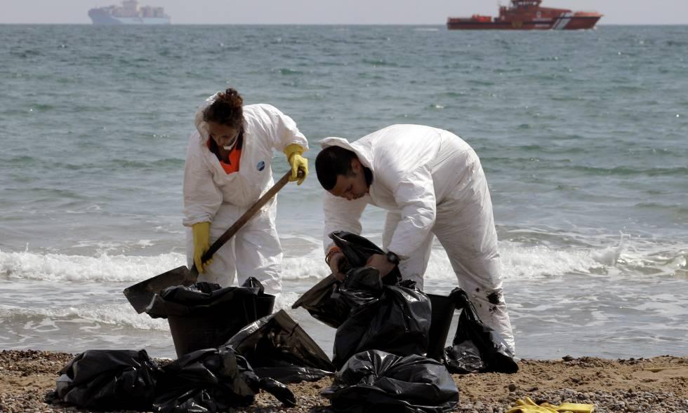 """Operarios de limpieza del Ayuntramiento de Valencia recogen """"galletas"""" de chapapote producidas por un vertido de fuel en la playa de El Saler, en abril de 2014. EFE rn"""