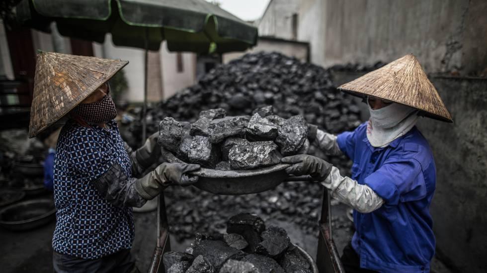 Dos mujeres rompen el carbón en piedras en una jornada de 10 horas por seis euros en Dai Bai, Vietnam.