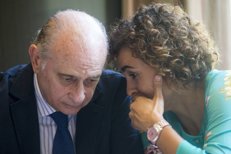La ministra de Sanidad, Dolors Montserrat, habla con el exministro del Interior Jorge Fernández Díaz.