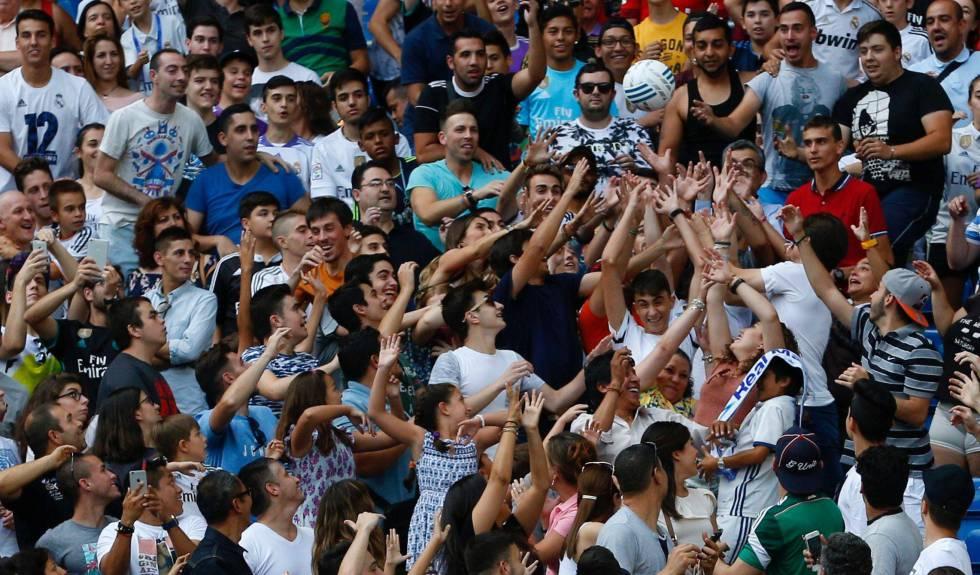 Aficionados en las gradas del Santiago Bernabéu luchan por un balón lanzado por Theo Hernández.