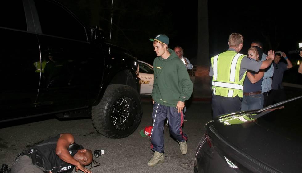 Justin Bieber pasa frente a su coche para comrobar el estado del fotógrafo herido.