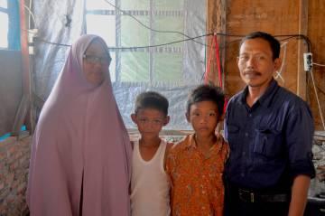 Dharma Diani con su familia en el barrio Pasar Ikan, al norte de Yakarta.