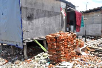 Ladrillos frente a una de las infraviviendas levantadas en el barrio de pescadores de Pasar Ikan, en Yakarta.