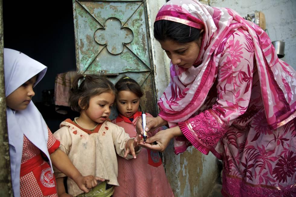 Una trabajadora sanitaria marca el dedo de una niña para indicar que ha sido vacunada contra la polio, en Karachi (Pakistán).