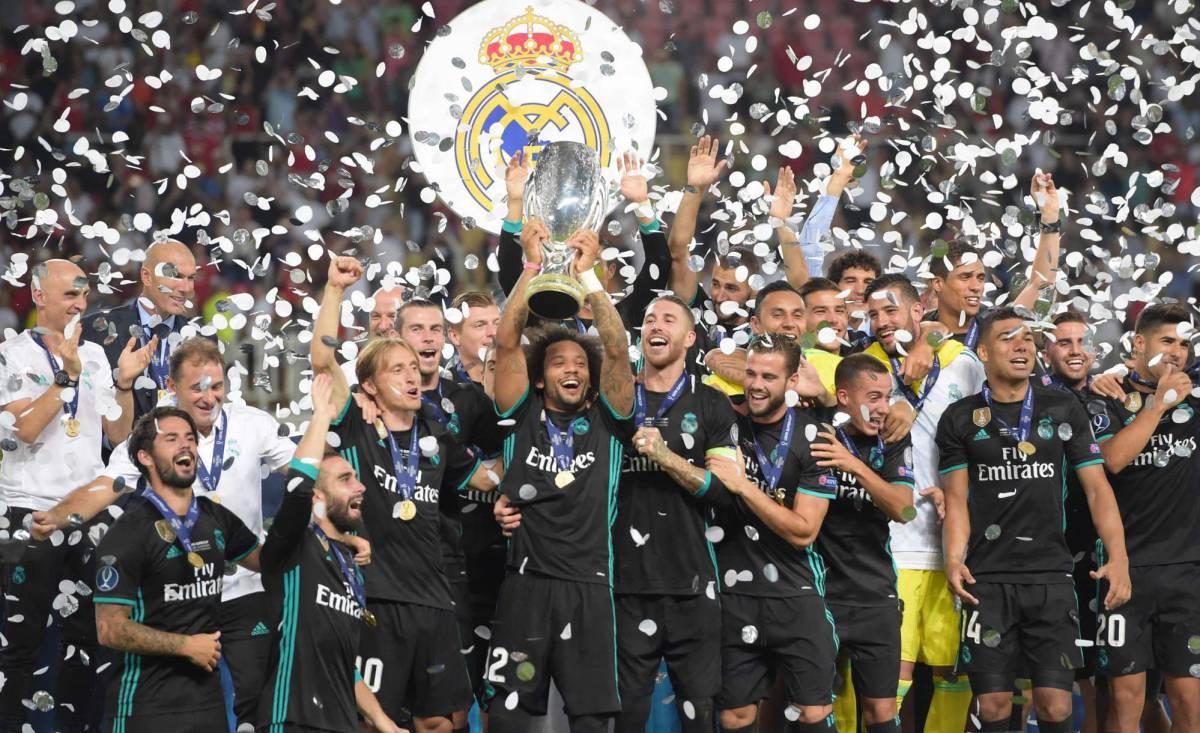Los jugadores del Madrid levantan el trofeo.