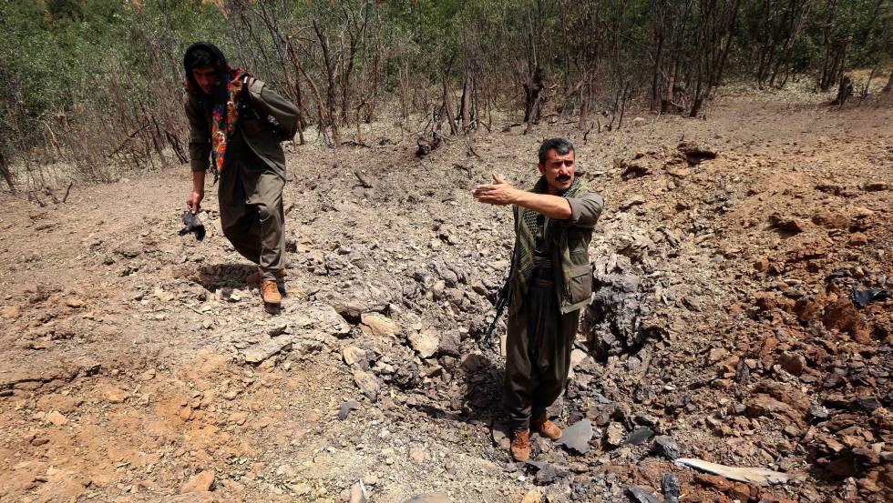 Milicianos del Partido de los Trabajadores del Kurdistán (PKK) inspeccionan un cráter causado por los bombardeos de los aviones del Ejército turco.