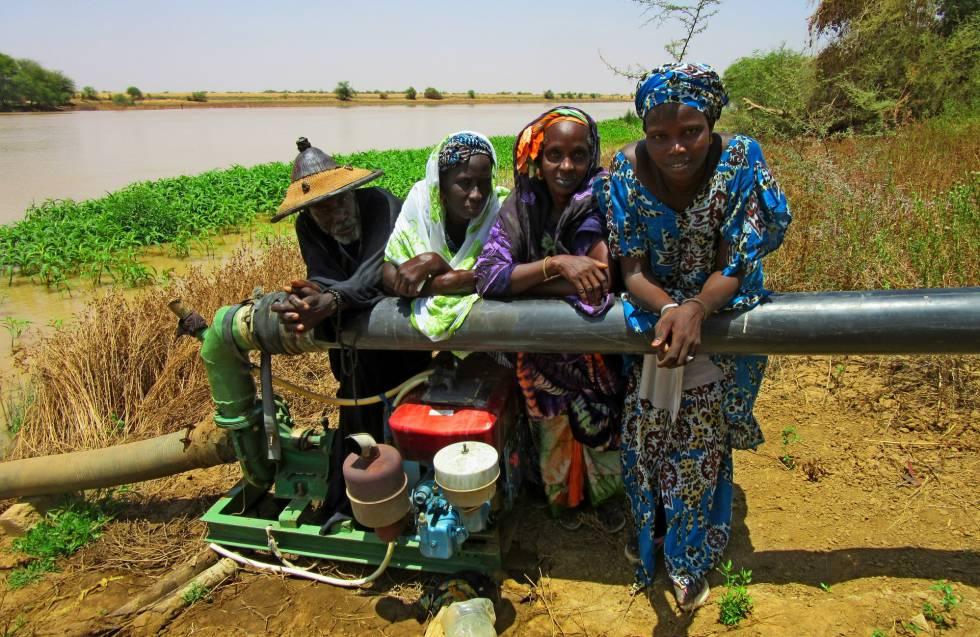 Djiby Ly, Djenaba Demba, Binta Cámara y Aminata Ba junto al río Doué y la bomba que extrae el agua para conducirlo a su huerto, en Guedé.