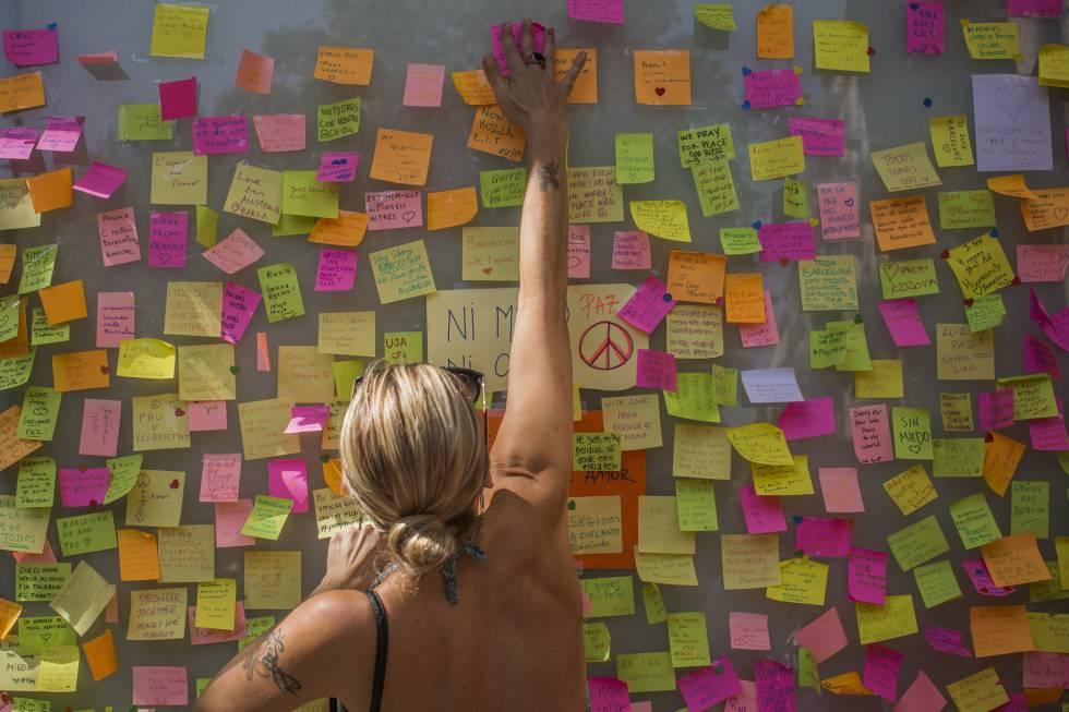 Una mujer deja un mensaje de homenaje en la Rambla.