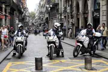 Three regional police officers block the entrance to a street near the La Rambla boulevard.