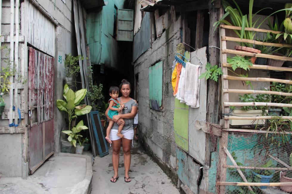 Jomarie Malonzo Palma, de 24 años, con su hijo delante de su hogar en Valenzuela, un distrito de Manila (Filipinas).