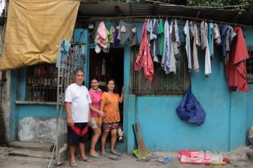 Nico Espinosa, presidente de la Asociación de vecinos de Valenzuela (Manila, Filipinas), posa con la familia delante de su tienda.