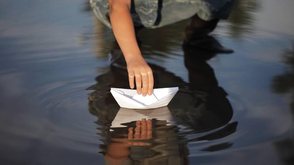 Un niño deposita un barco de papel en el agua.