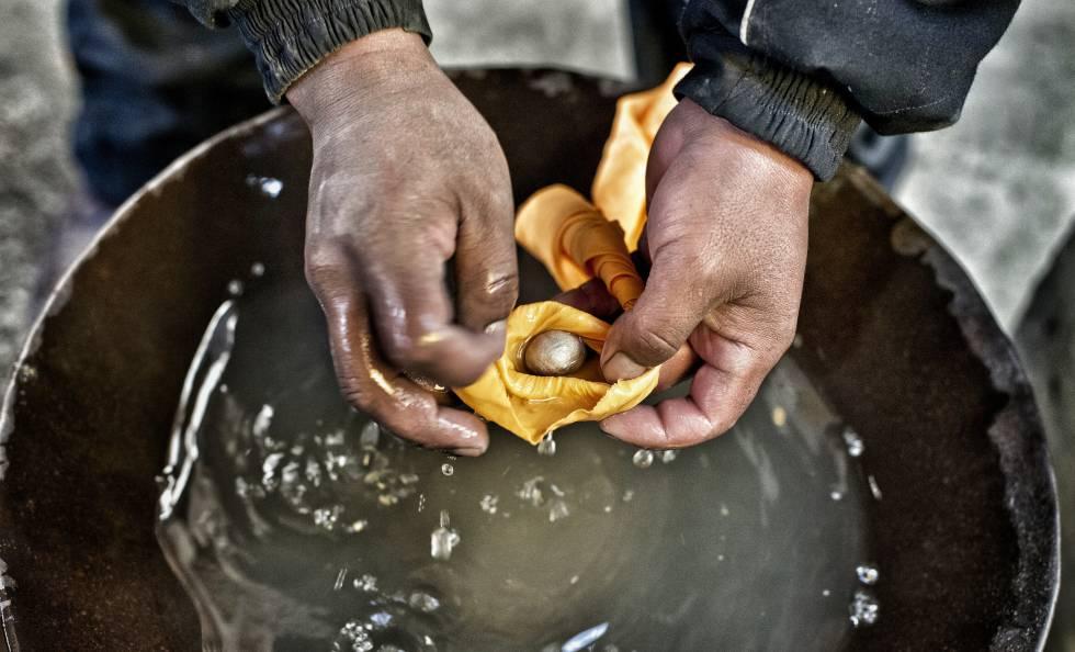 Con un pañuelo se filtra el agua hasta que queda en la mano una pequeña bola de mercurio y oro.