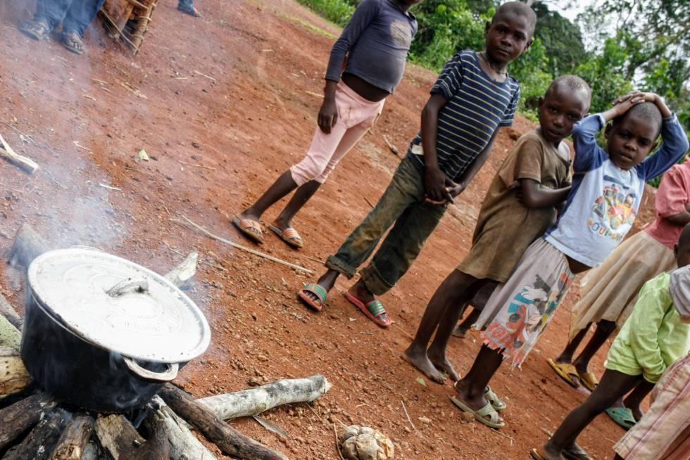 Los niños esperan impacientes a que se cocine la papilla.