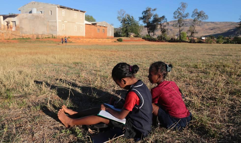 Dos niñas hacen los deberes en el campo, en Madagascar.
