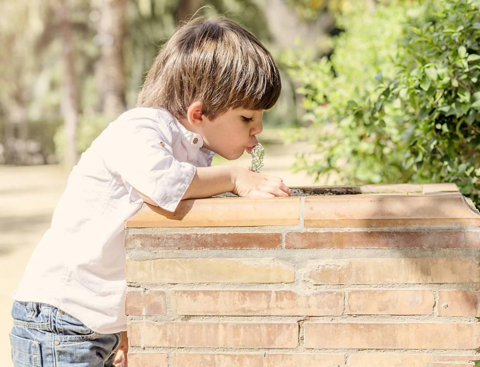 Un niño bebe agua de una fuente.