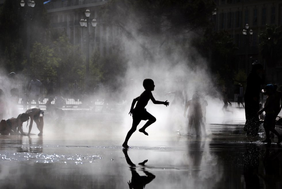 Un niño juega entre la niebla producida por una fuente en el sur de Francia, el 2 de agosto de 2017.